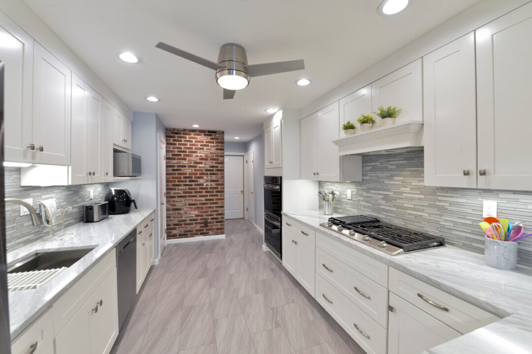 galley kitchen with brick accent wall and modern fan