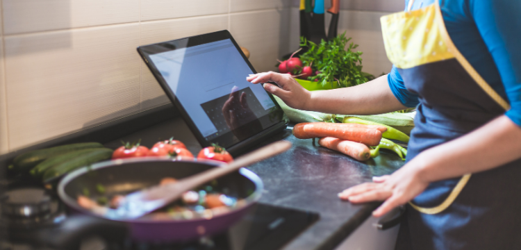 Woman Cooking in Kitchen Using Laptop for Recipe Guidance